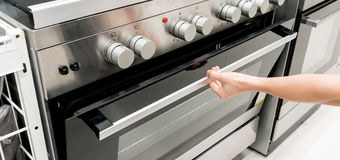 Woman's hands open the black and silver door of oven machine for cooking