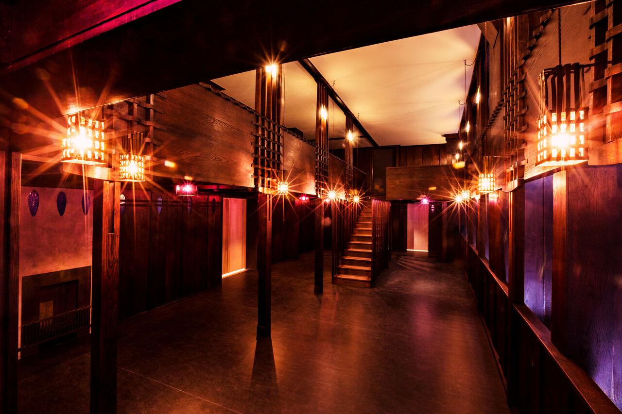 麦金托什的橡木厅,全部是深色木板和紫色玻璃。 厅内有一个到上层的楼梯。