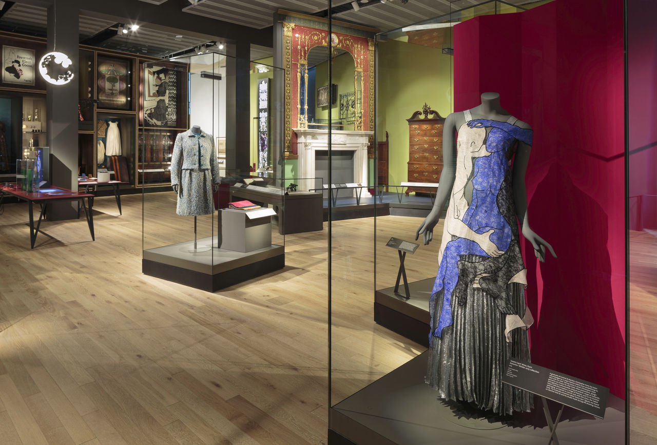 A wide shot of a museum gallery, you can see several objects including a dress, a fireplace and other textile pieces.