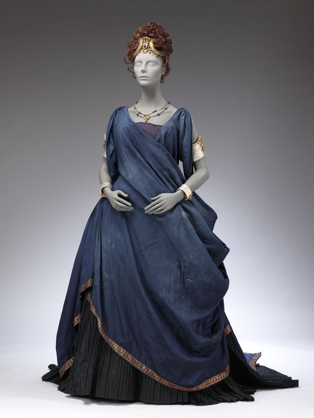 Long blue dress on a grey mannequin. The dress has many folds and a long train.