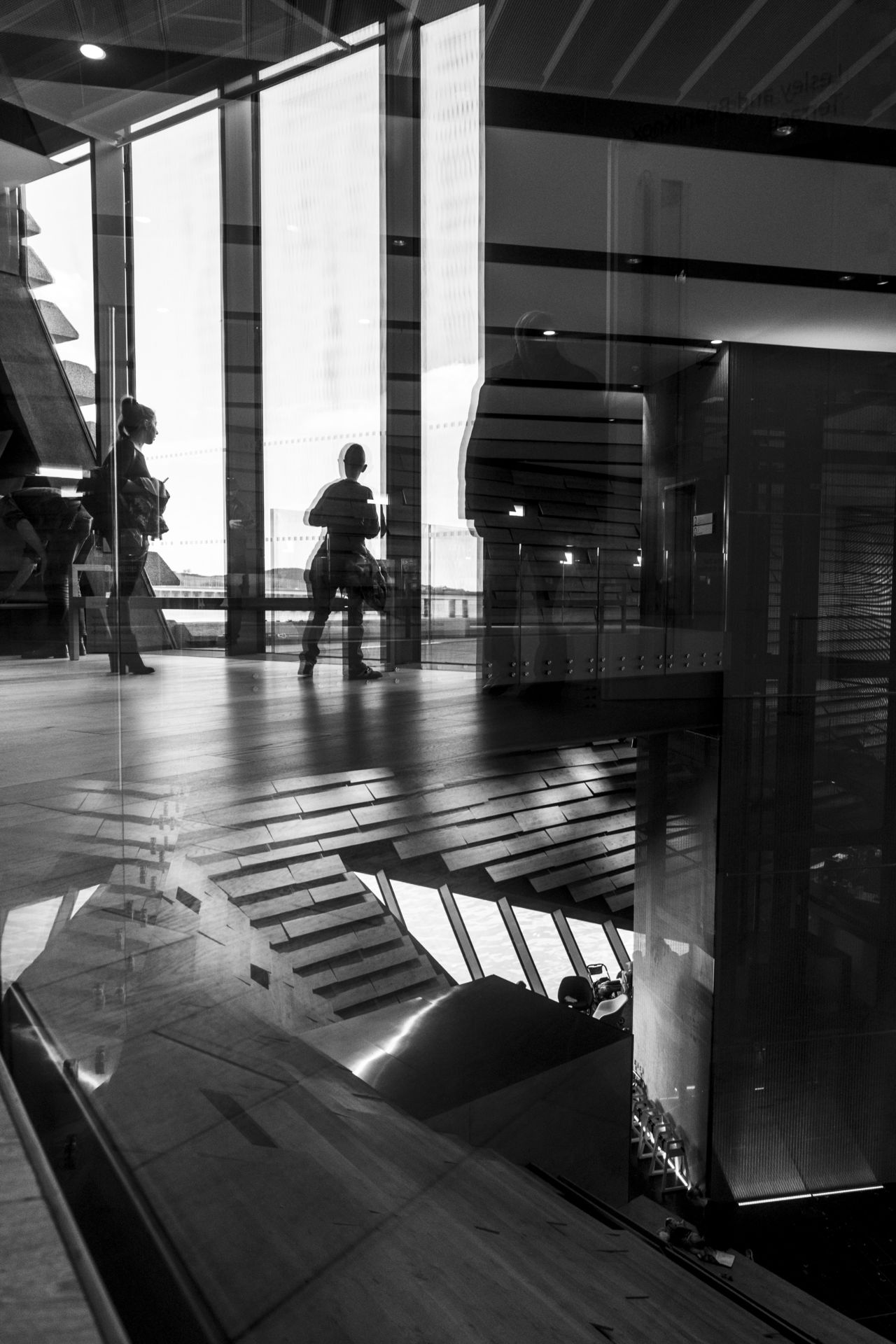 A photo taken in V&A Dundee of a reflection in a glass balustrade, showing the upper hall's large windows and people milling about. Through the glass, you can make out the lower hall and the lift shaft. Black and white.