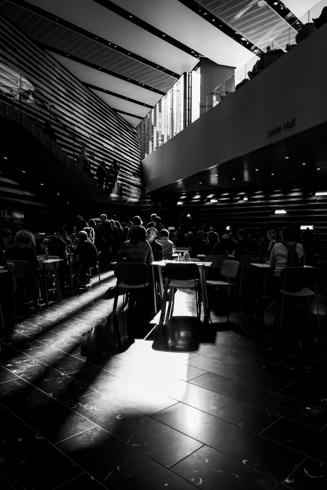 A photo of V&A Dundee's cafe with people sitting at tables with the high ceiling and striated architecture filling the backdrop. Black and white.