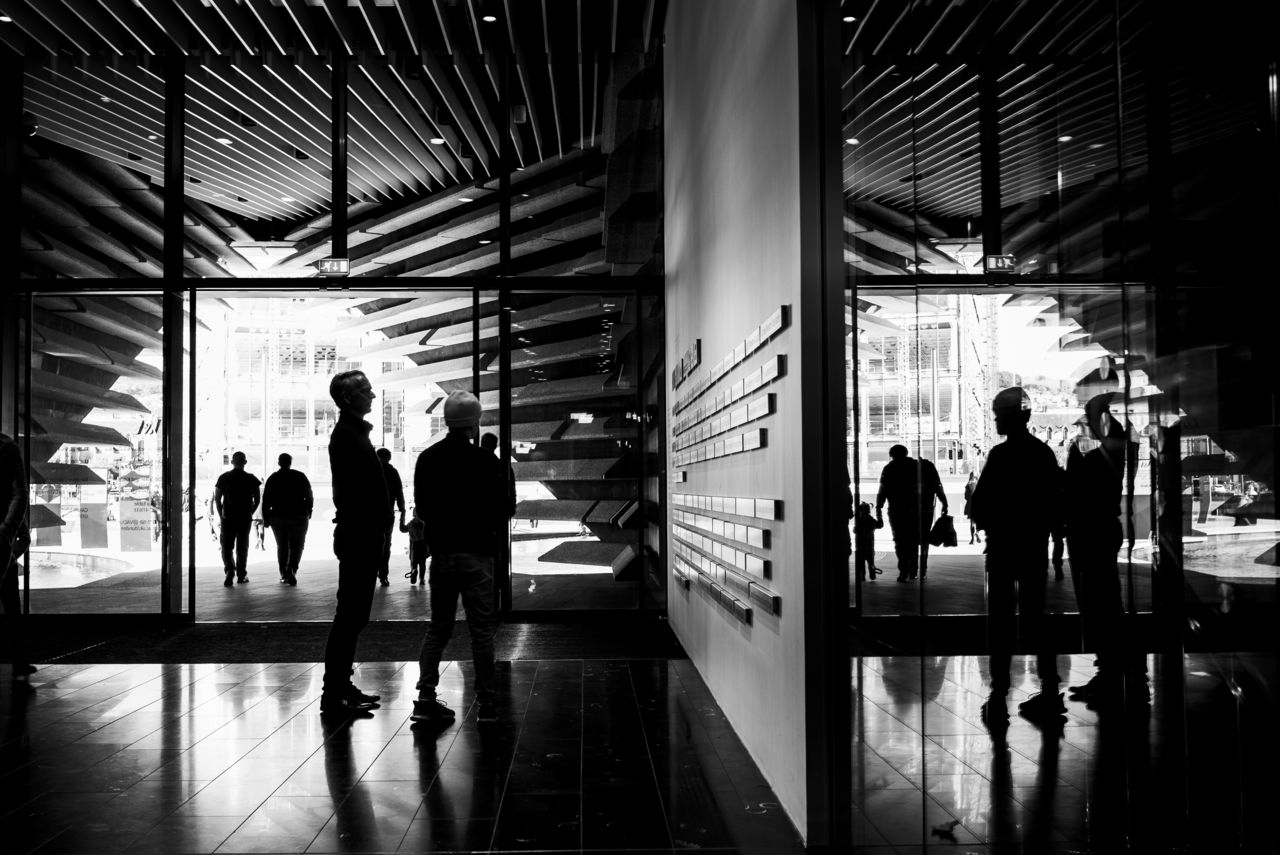 People gathering in the foyer of V&A Dundee, reflected back in its glass doors. Black and white.