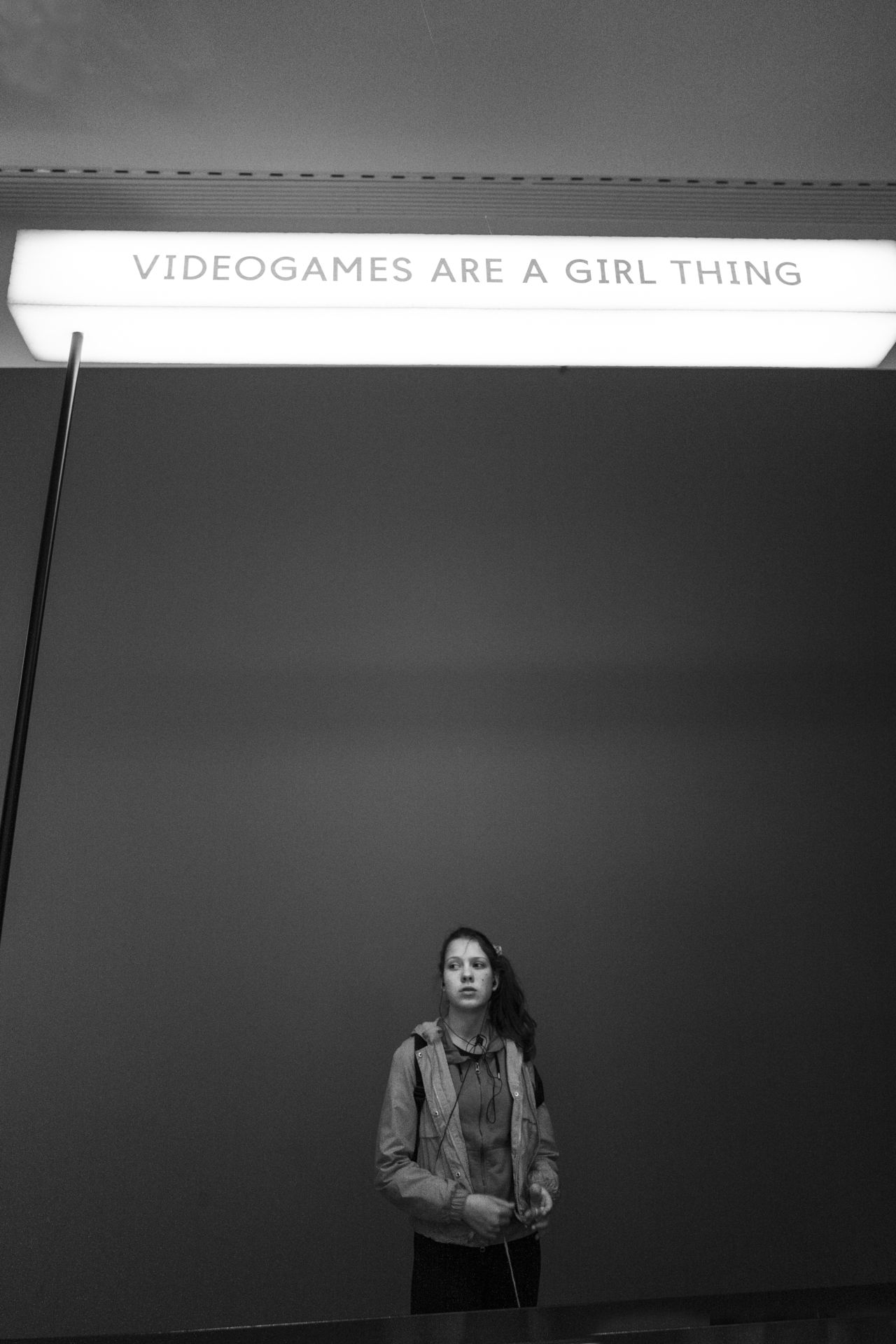 "A photo of a woman standing against a grey wall with a lightbox above her head. The text on the box reads ""Videogames are a girl thing"". Black and white."
