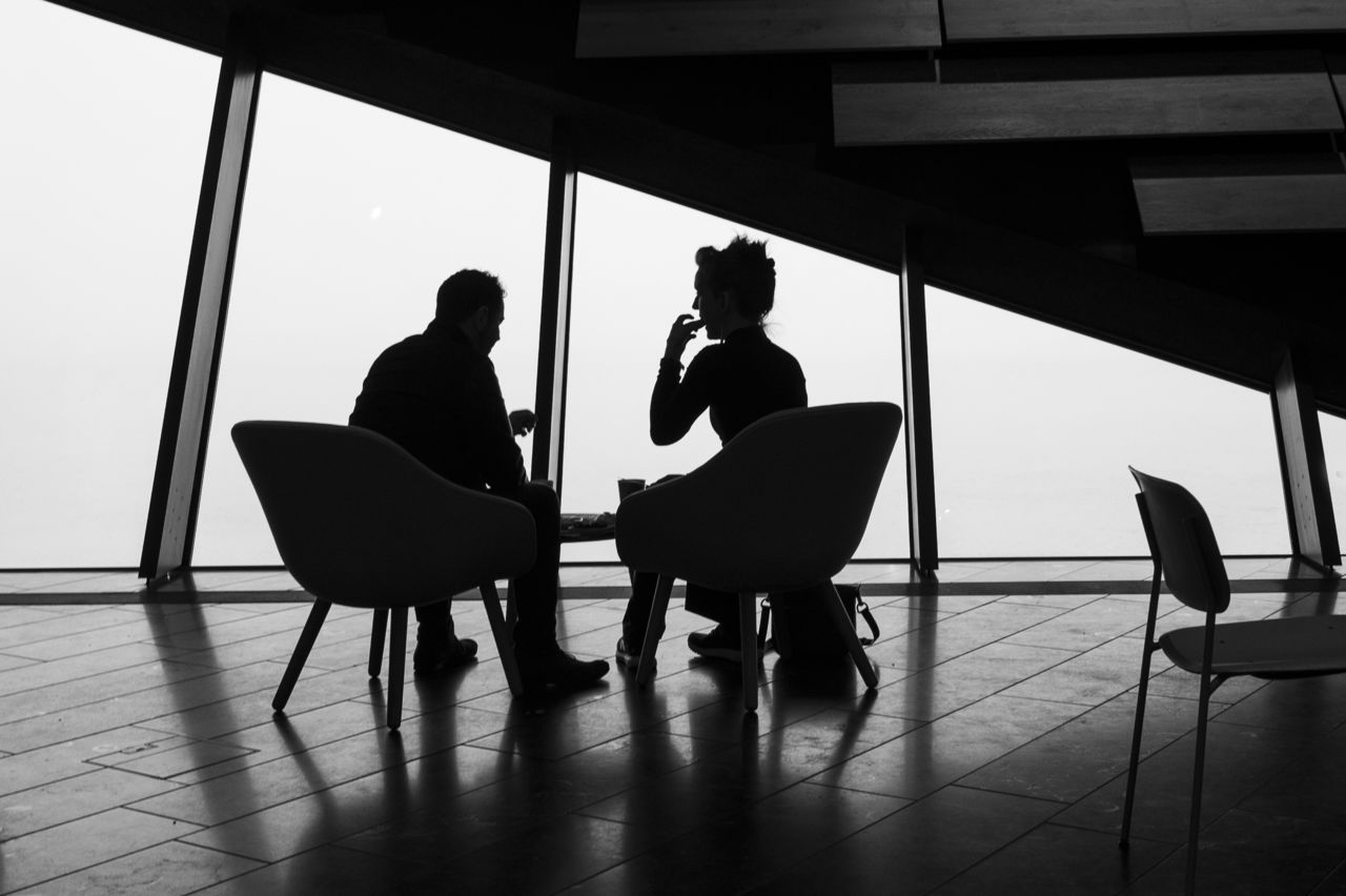 Two people sat at a table inside V&A Dundee, in silhouette against a window. Black and white.