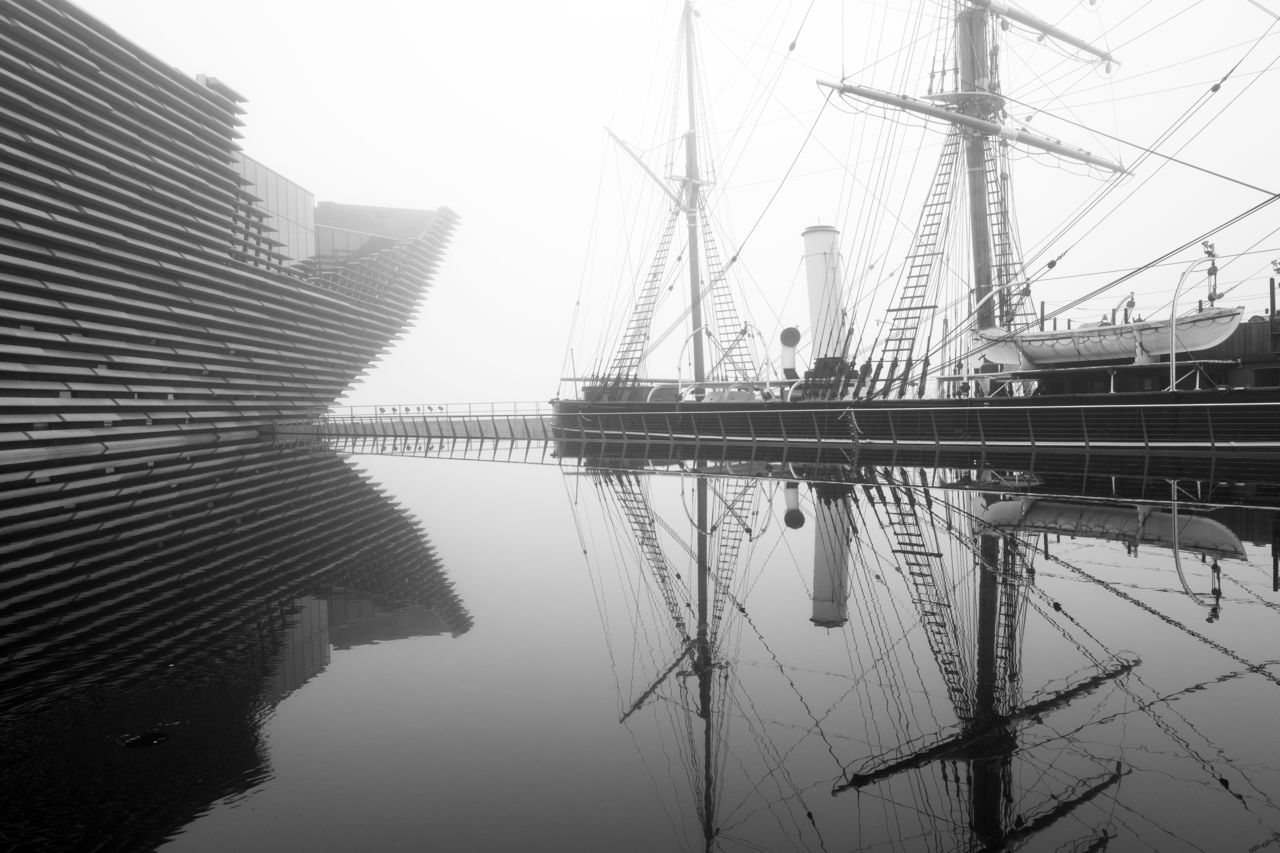 V&A Dundee and its neighbour RRS Discovery in the mist. Both are reflected in V&A Dundee's pools. Black and white.