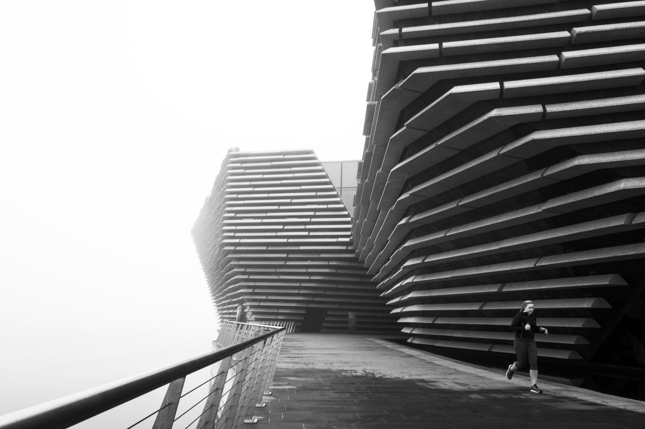 External shot of V&A Dundee in the mist. A runner runs past. Black and white.