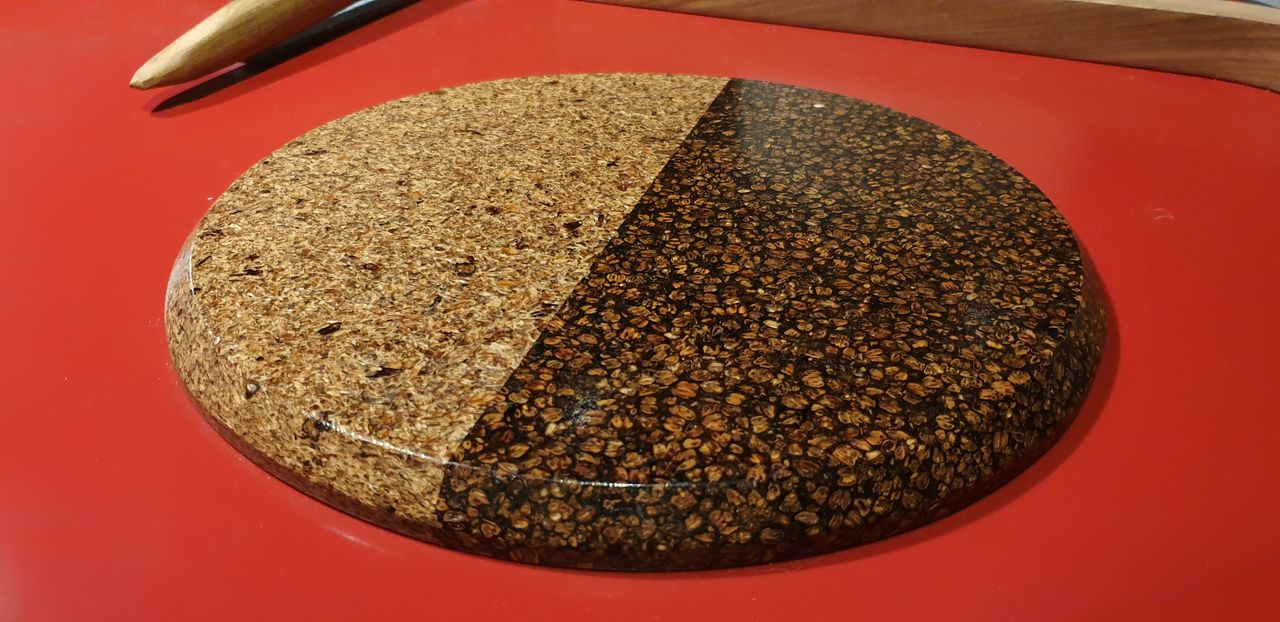 A circular piece of polished surface made from brewing waste. Half the circle is light-coloured and half is dark, due to the materials each side is made from. The circle sits on a bright red table top.