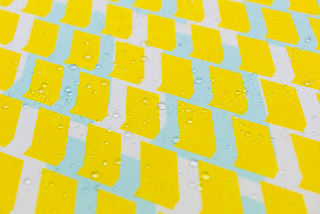 Close-up of bright yellow and blue fabric with a vibrant pattern of shapes on it. There are neat, round water droplets sat on the fabric.
