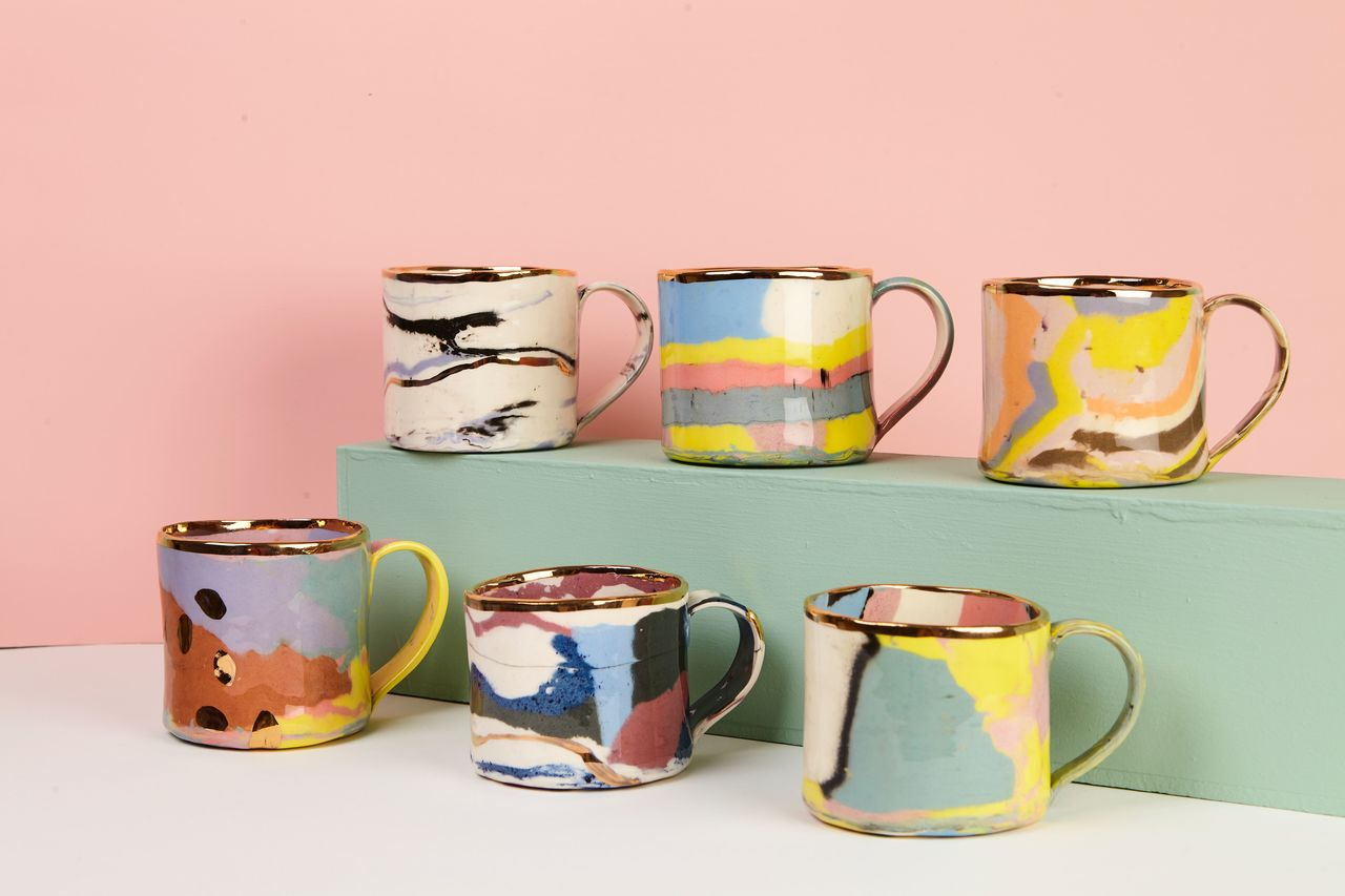 Pink background with painted mugs in front of it.