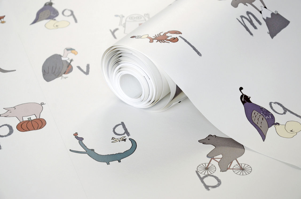 A roll of pretty wallpaper with animal characters on it.