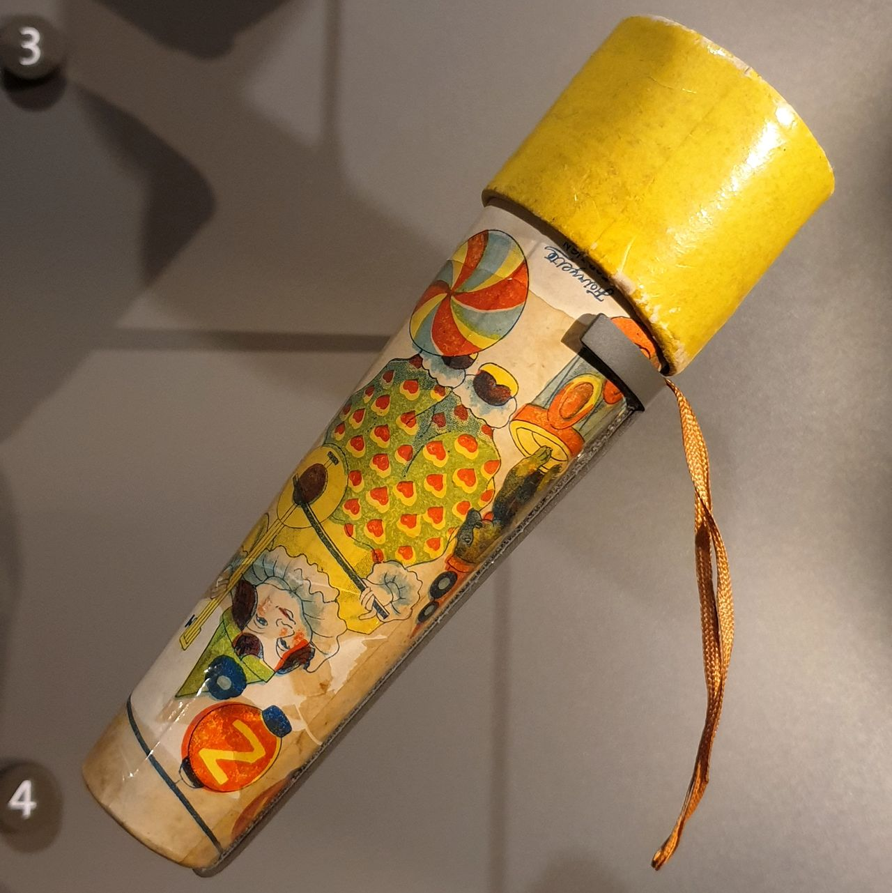 A small kaleidoscope. Looks like a conical tube covered in colourful paper with a circus-like scene, including a clown-like musician, a seal on a platform, etc.