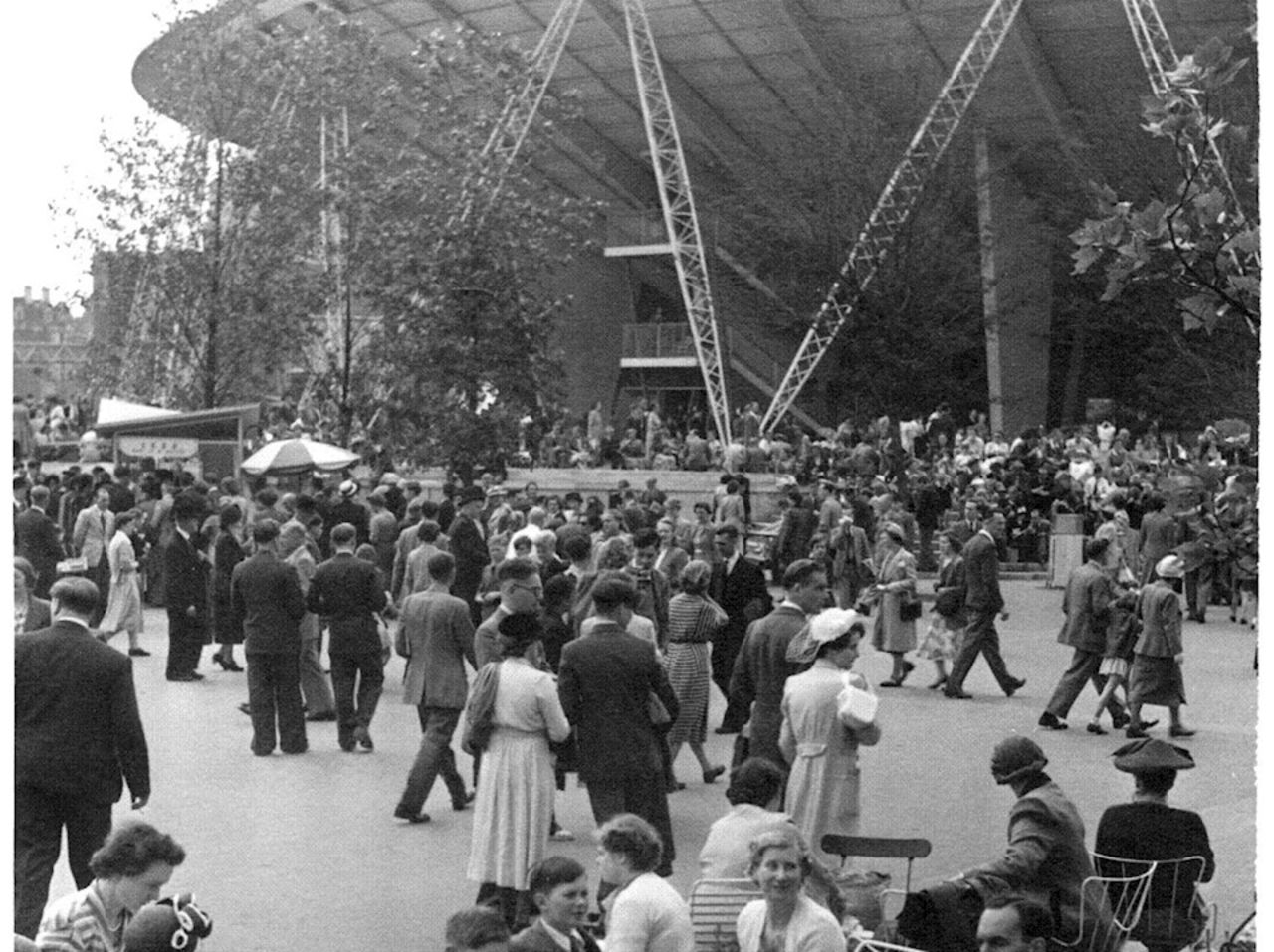 Black and white photo of crowds of people in 1951 gathering next to a large stadium.