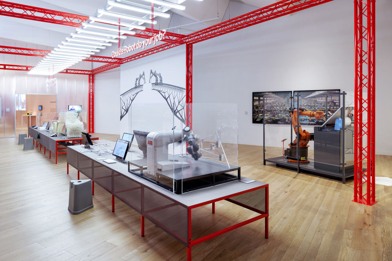 Photo of the Hello Robot exhibition with cases and tables with robot related objects on them.