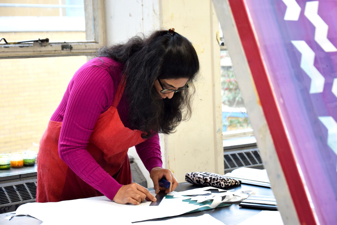 A woman at a worktable working on textile design.