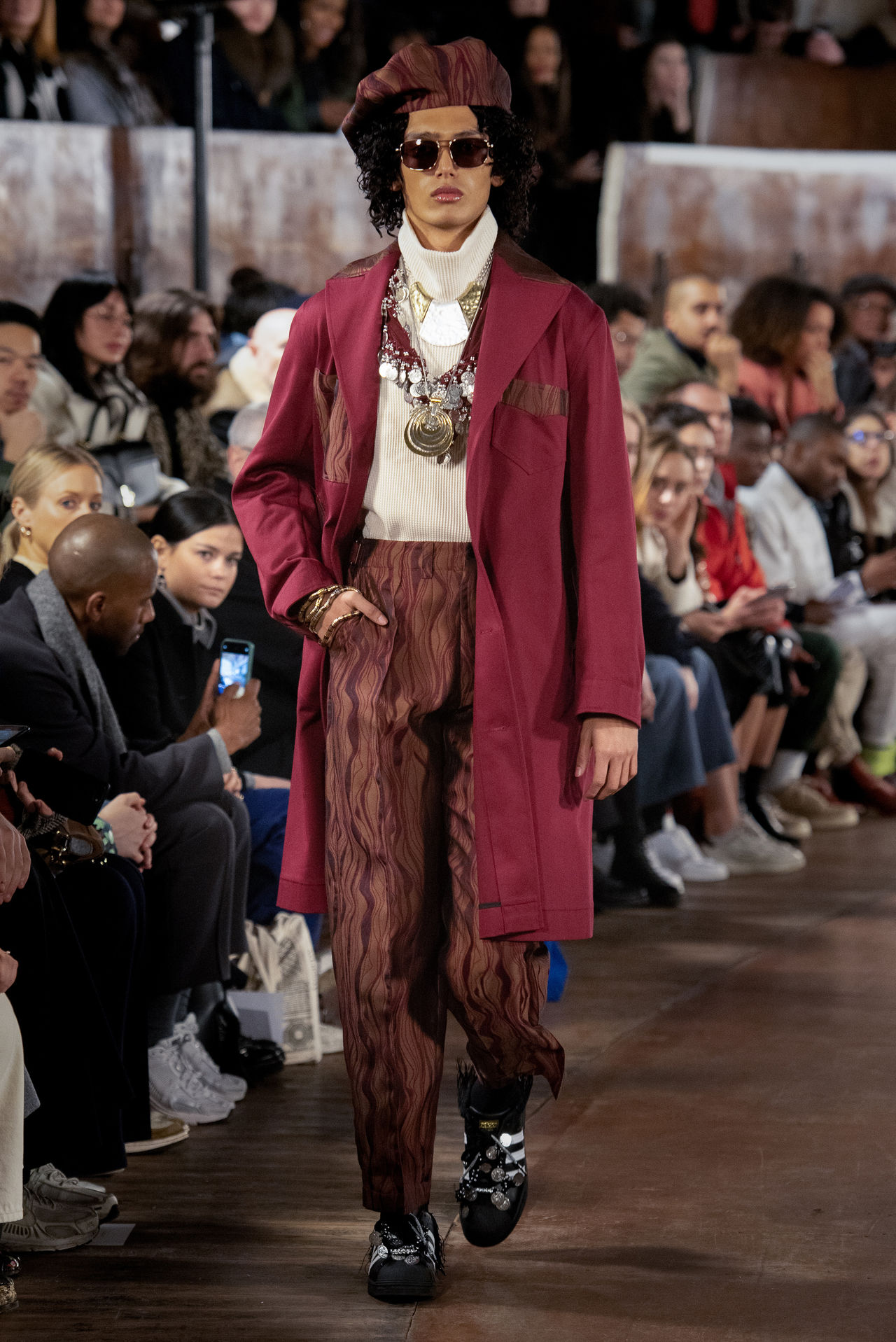 A model walking down the runway wearing Nicholas Daley's Autumn Winter 2020 collection. This look is a long maroon coat with stunning trousers in a painterly style.