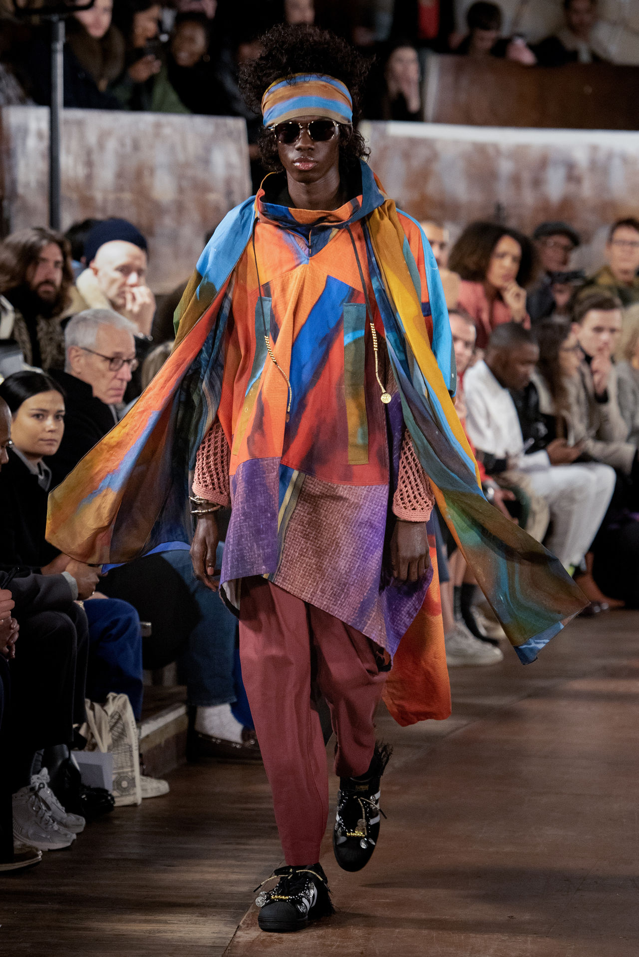 A model walking down the runway wearing Nicholas Daley's Autumn Winter 2020 collection. This look is a riot of colour and flowing print.