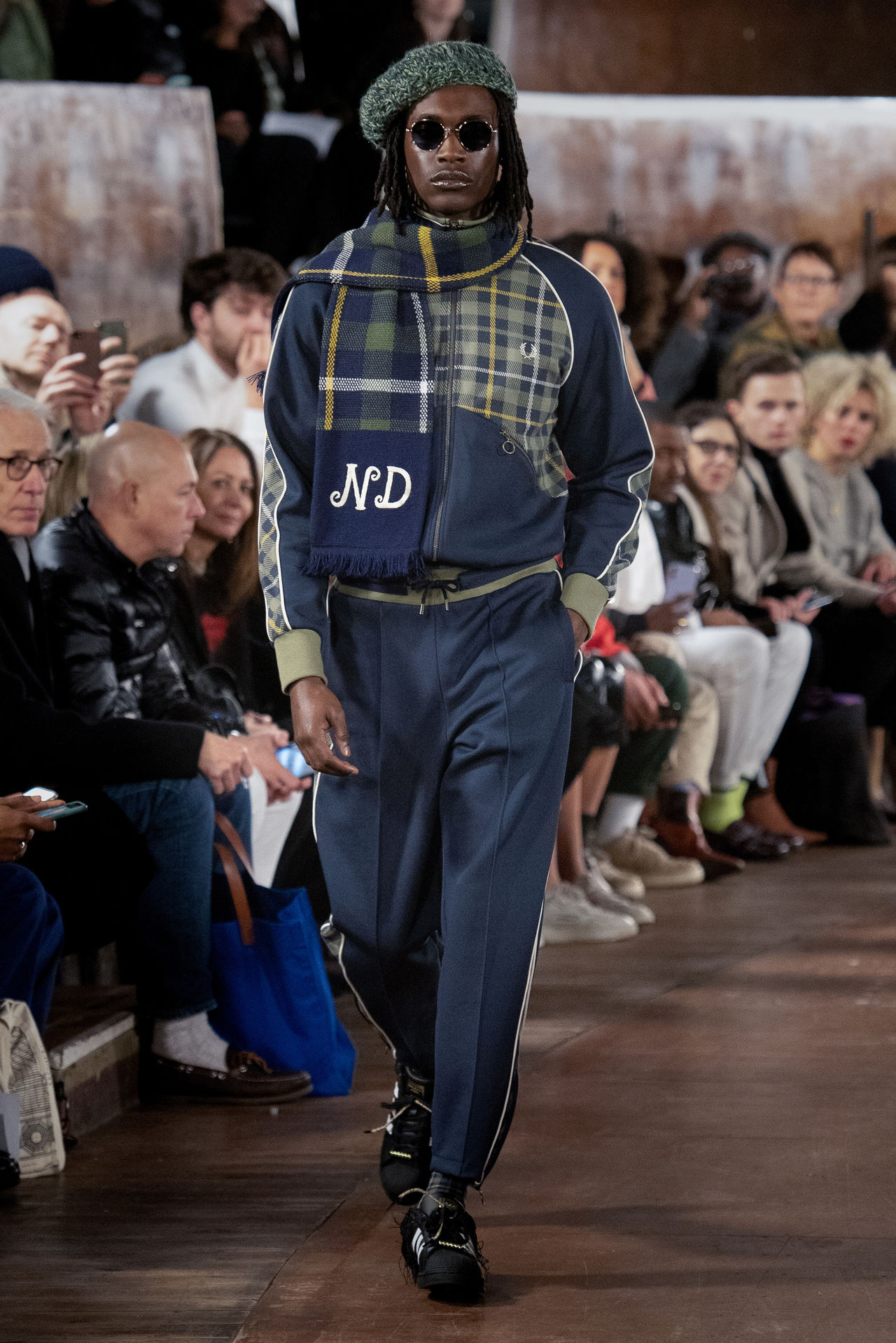 A model walking down the runway wearing Nicholas Daley's Autumn Winter 2020 collection. This look has dark greens and blues. A scarf worn by the model has the initials ND embroidered on it.