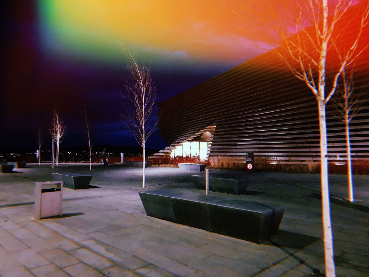 V&A Dundee at night, all dark with pockets of light.