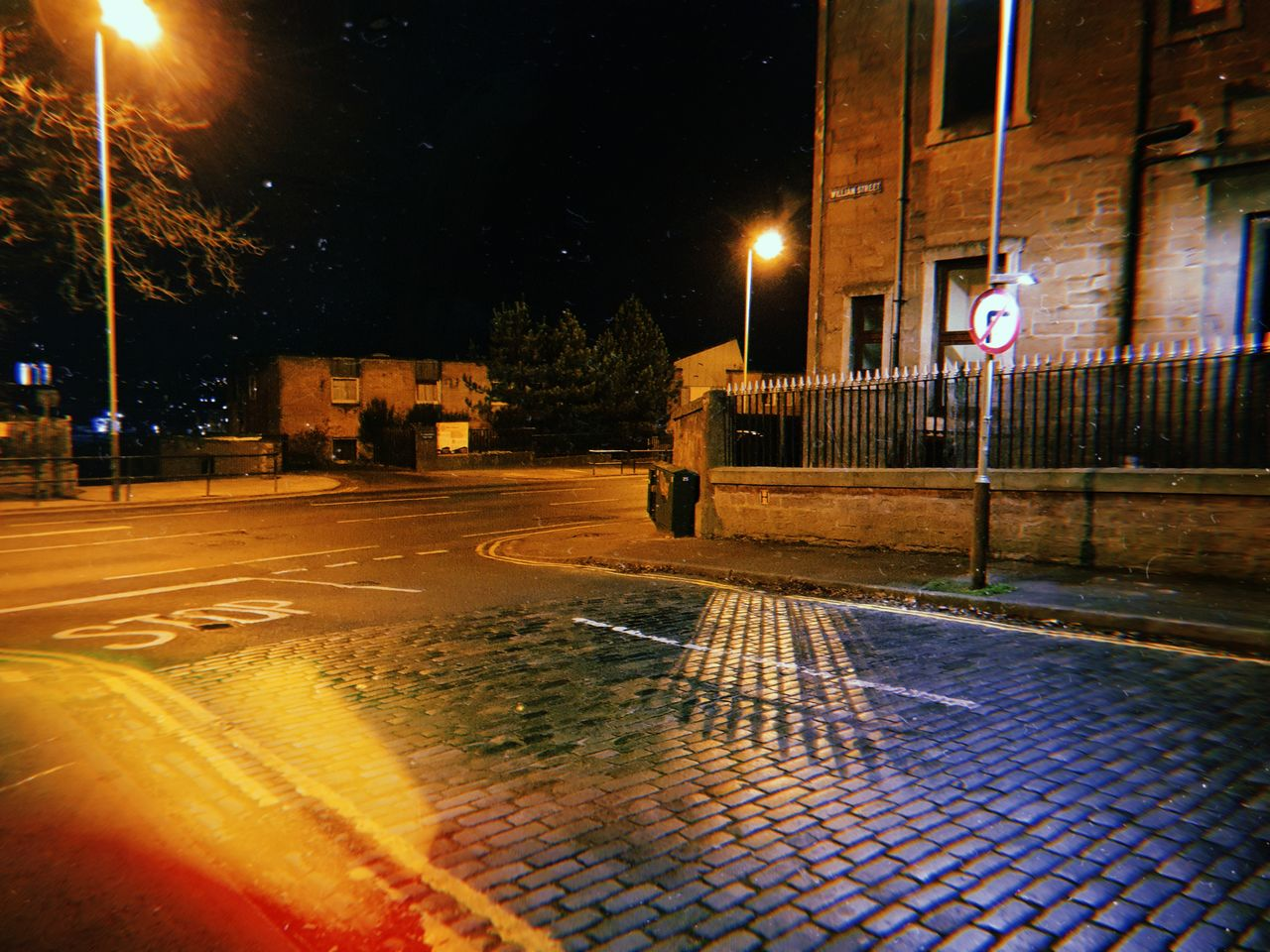A dark street in Dundee at night. The road is cobbled and the streetlight lights up part of it with the rest in darkness.