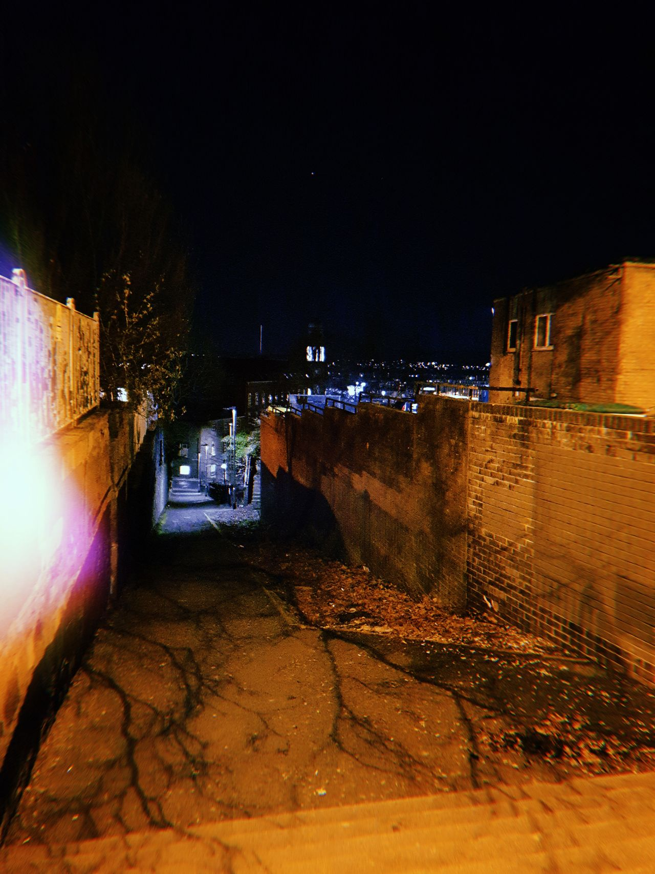 A dark alleyway in Dundee at night. The streetlight lights up part of it with the rest in darkness.