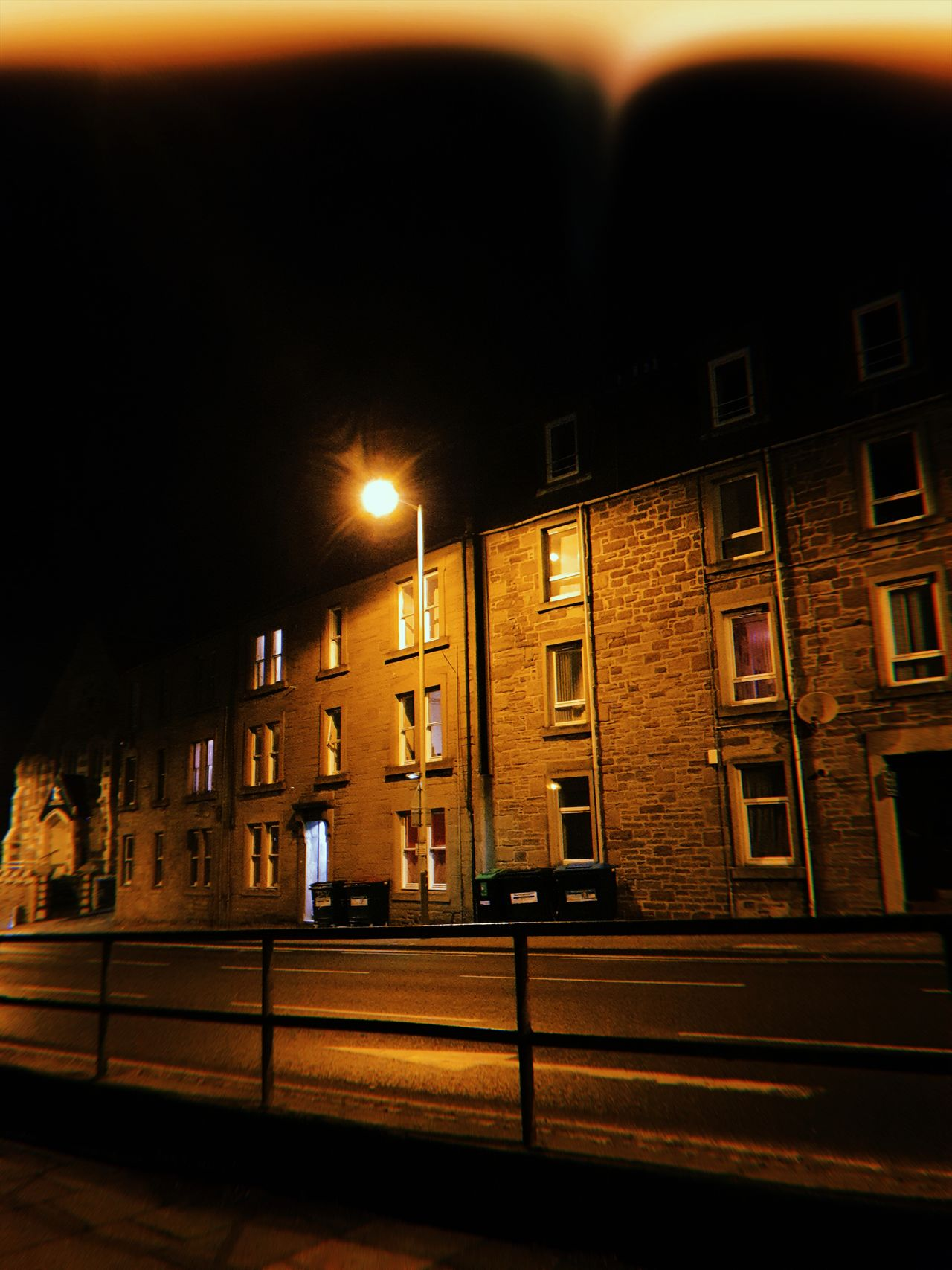 A dark street in Dundee at night. The streetlight lights up part of it with the rest in darkness.