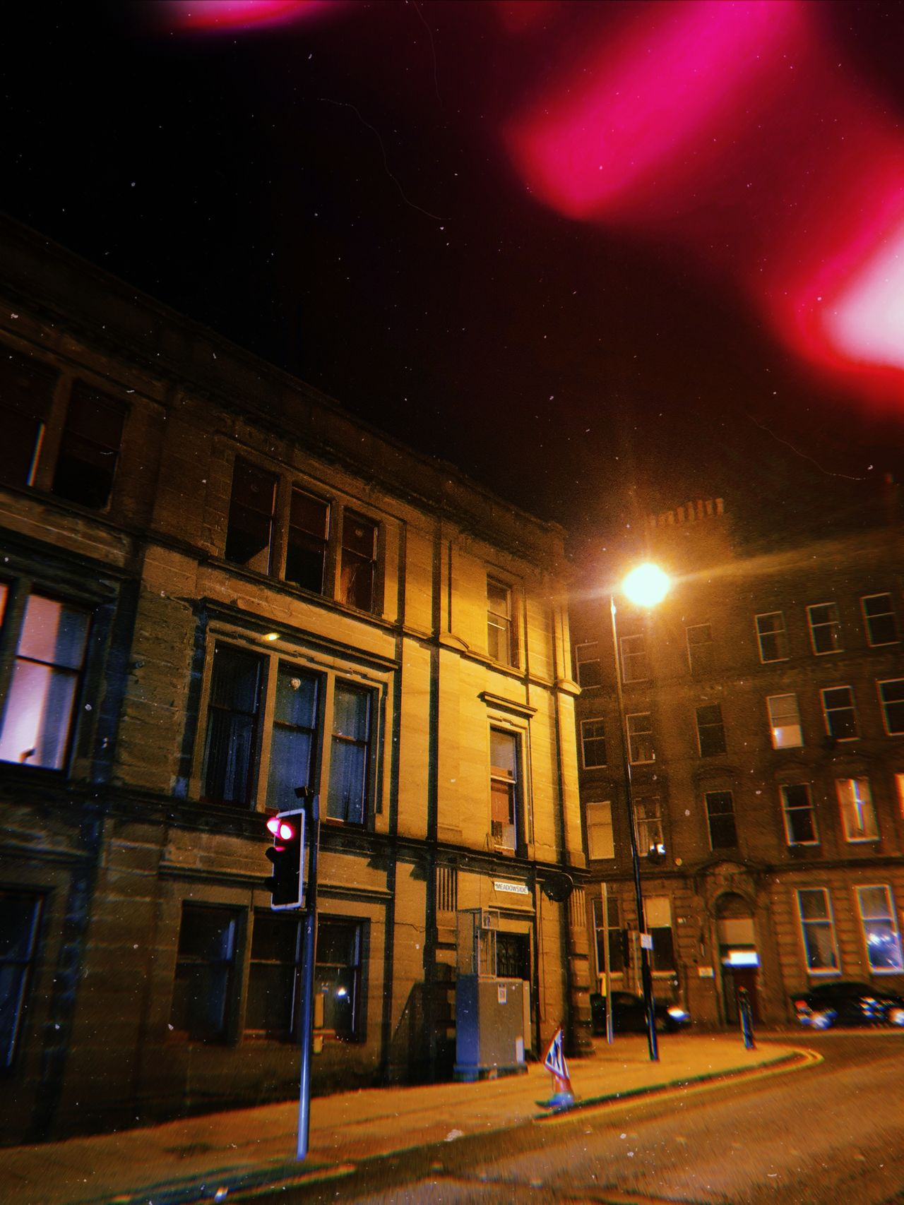 A dark street in Dundee at night looking up at a building.