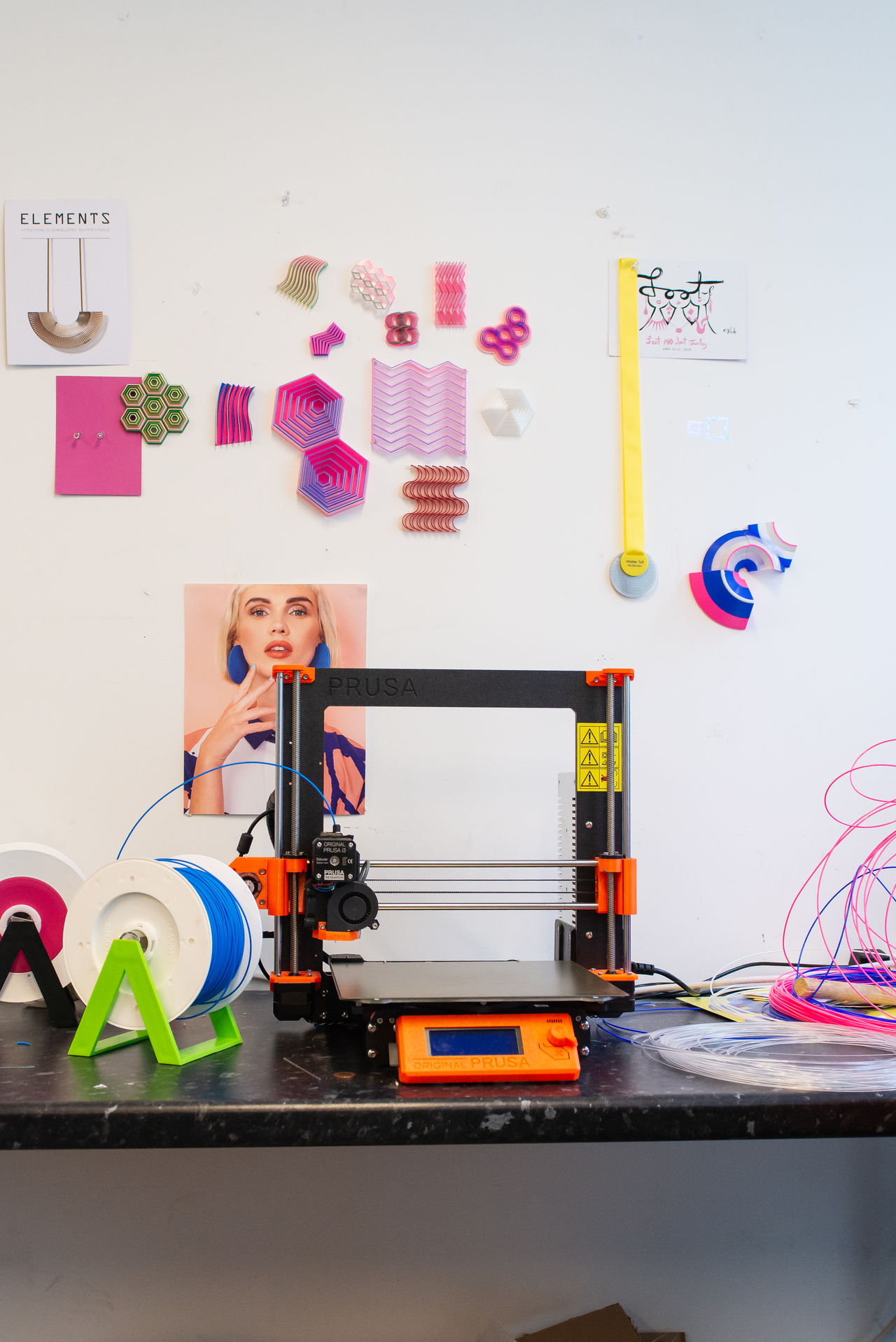 A desk on which sits an orange 3D printer. On the wall behind, posters and pieces of jewellery are hung.