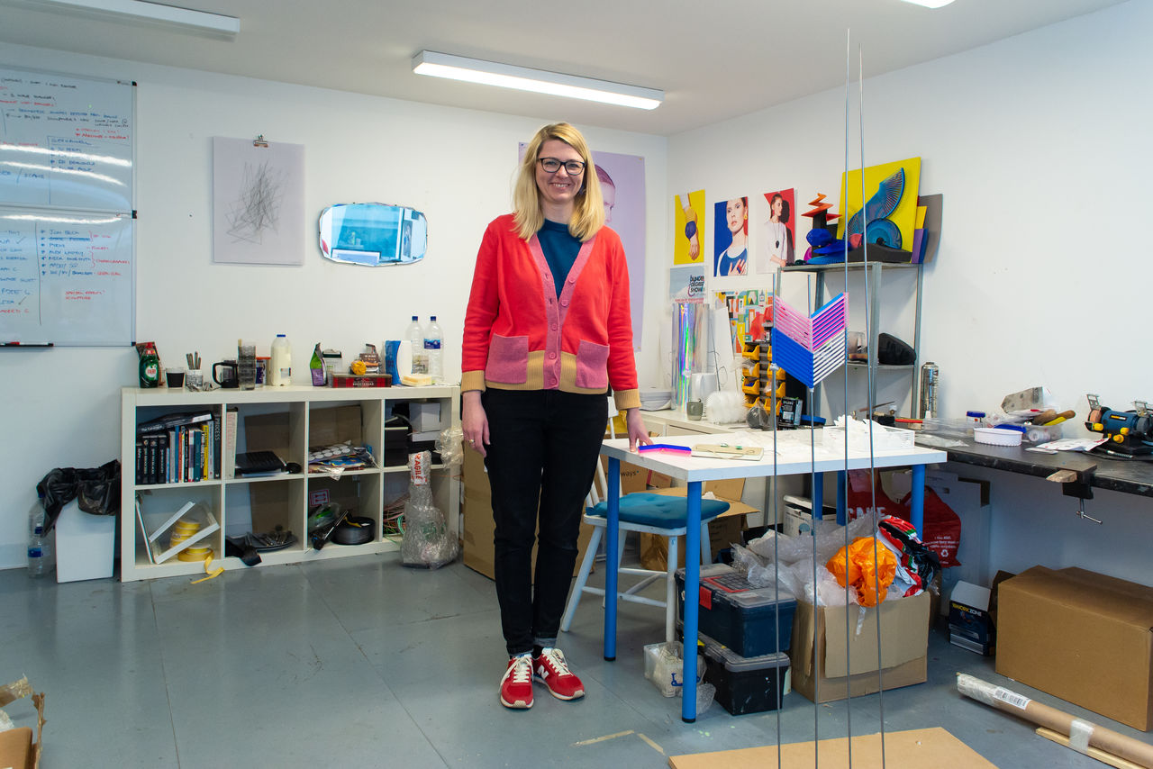 A woman in a coral cardigan stood ina . studio surrounded by interesting plastic structures of different colours.
