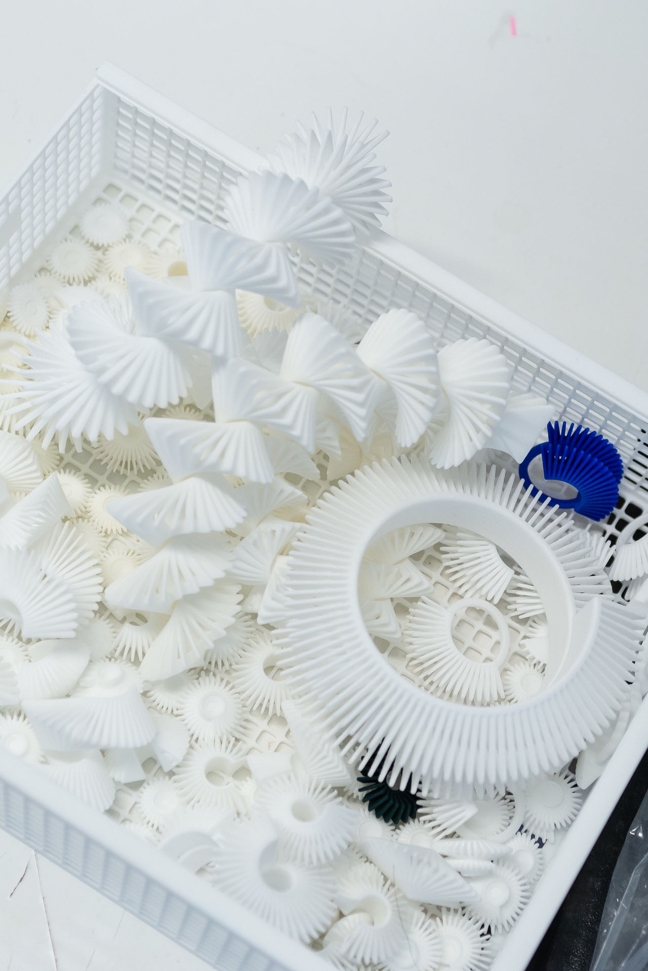 A box of white plastic geometric jewellery, all different shapes and sizes.