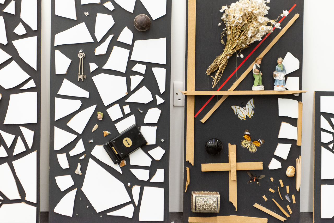 Black boards with broken porcelain, dried flowers, pieces of wood and other curious elements mounted on them.