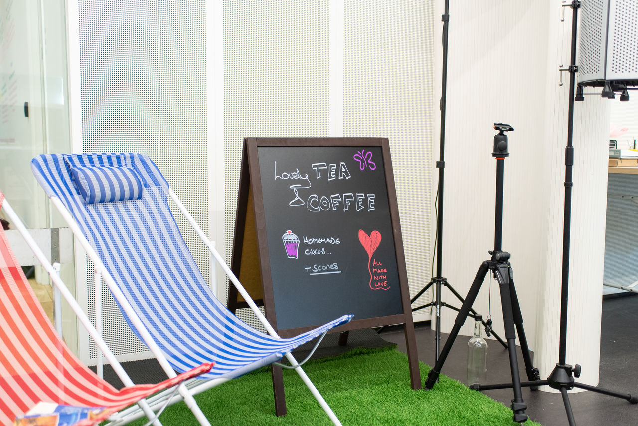 "Deck chairs sitting on artificial turf with a sandwich board next to them. On the board is ""Tea and coffee"" written in chalk."