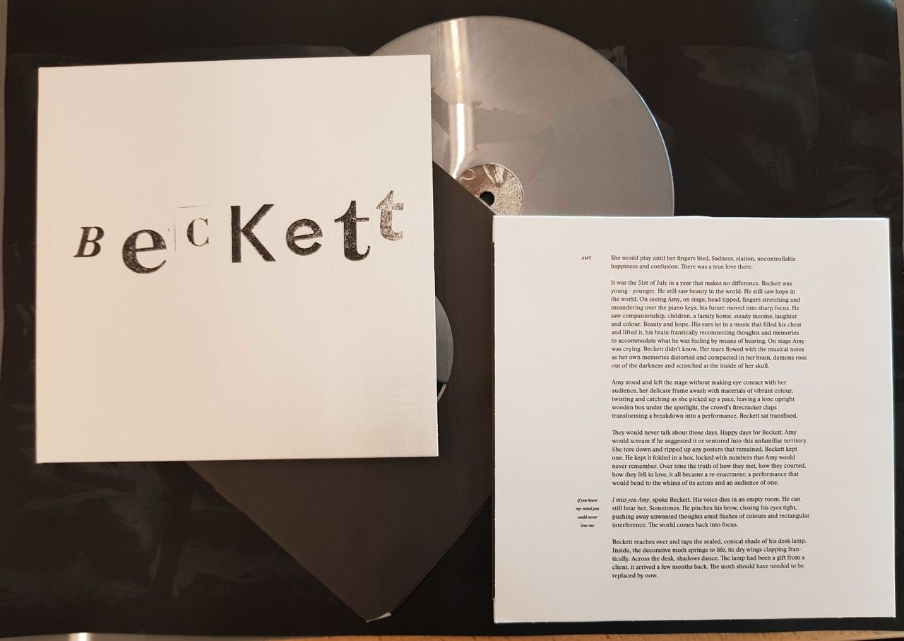 A silver record peeping out of its white sleeve, along with a book open with writing on it.
