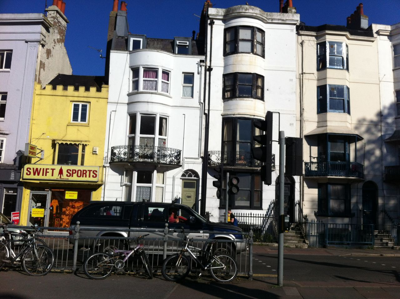 Terrace of large houses and one of them has the cast iron balcony over the top of one of its bay windows.