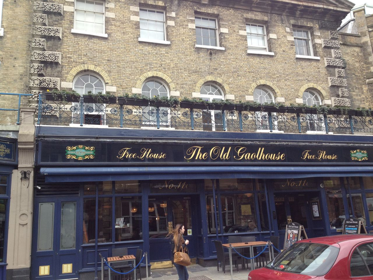 The balcony on the top of a pub adorned with the cast ironwork.