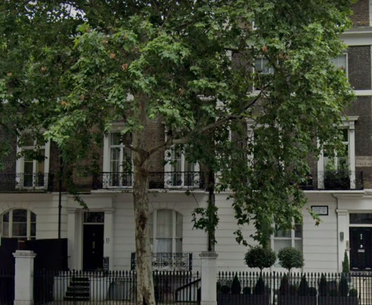 A terrace of houses in London, behind large trees, with the balcony adoring them.