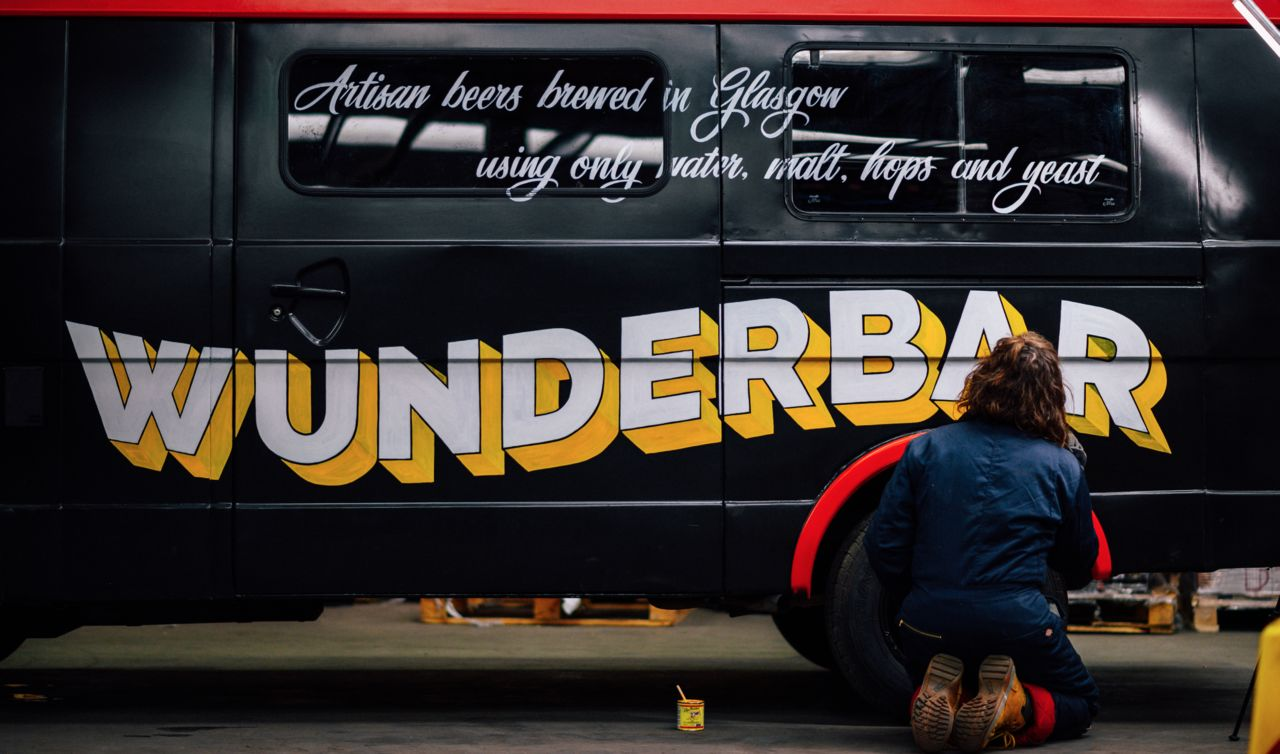 "Rachel kneeling beside a black van painting a sign on the sign that says ""Wunderbar""."
