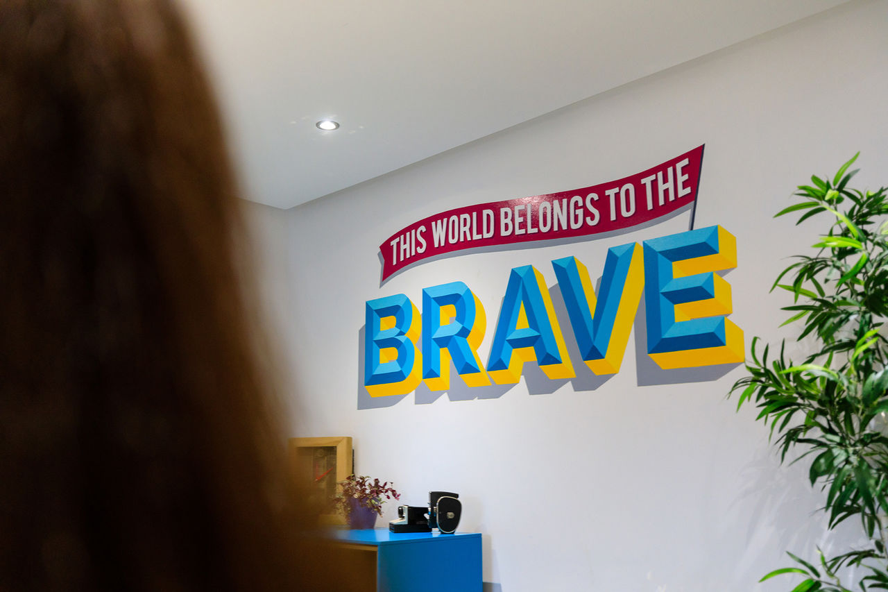"Colourful sign on the wall that reads ""This world belongs to the brave""."