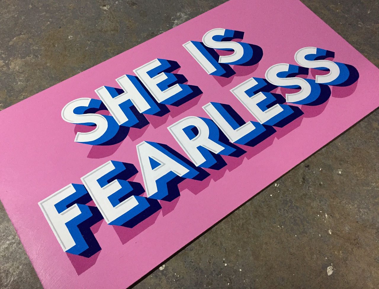 "A bright pink sign with blue letters saying ""She is fearless""."