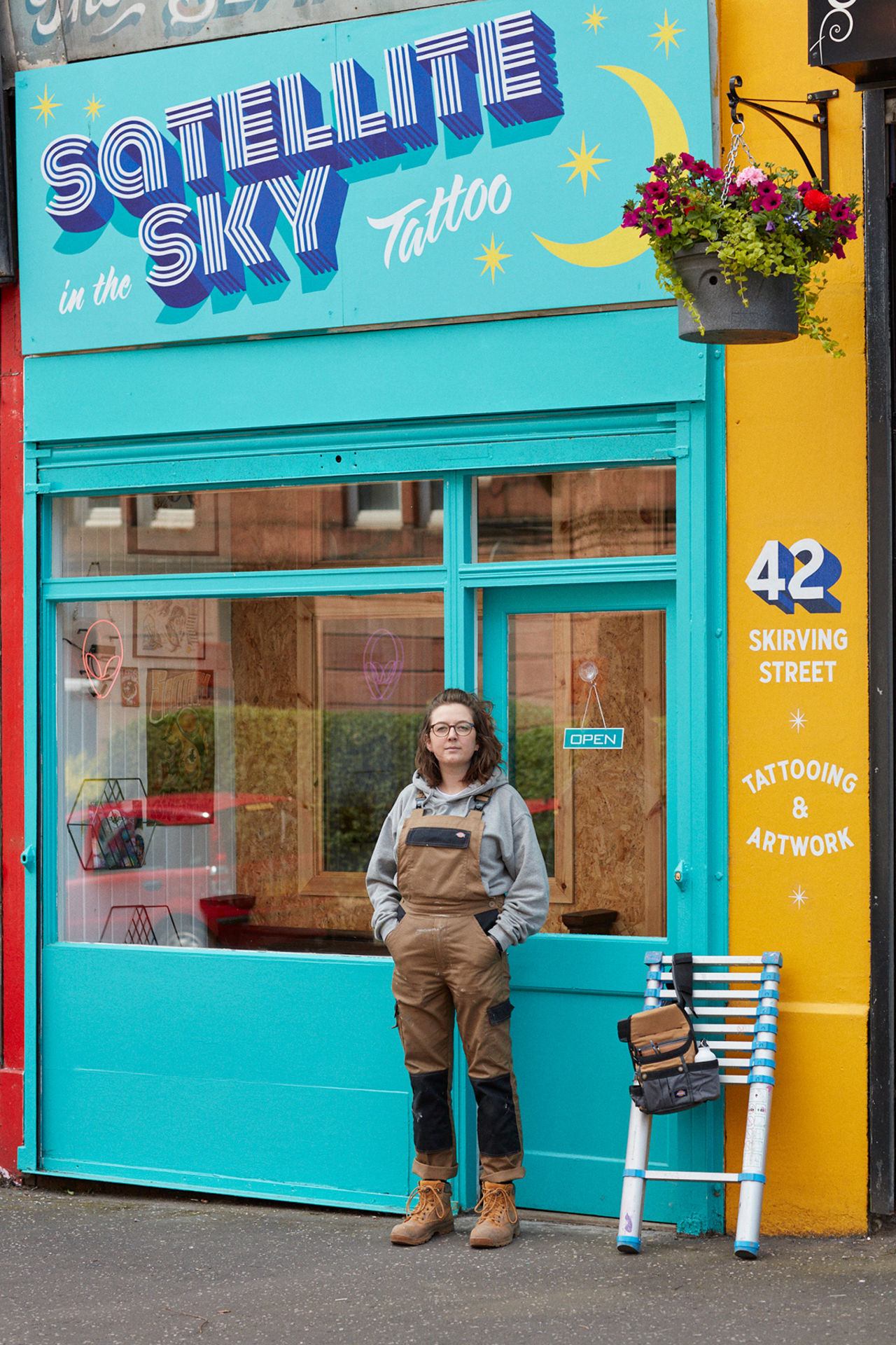 Rachel stood in front of a tattoo shop window where she's painted the sign in blues and yellows.