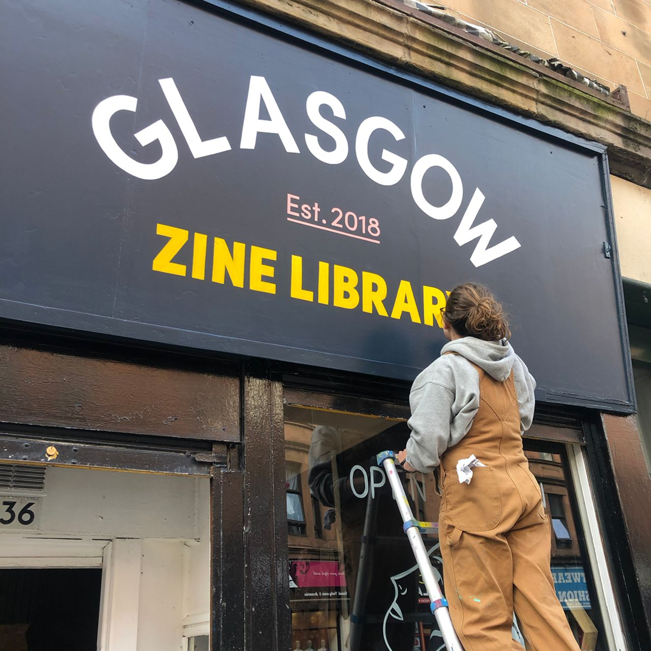 "Rachel up a ladder painting a large shop sign that reads ""Glasgow Zine Library""."