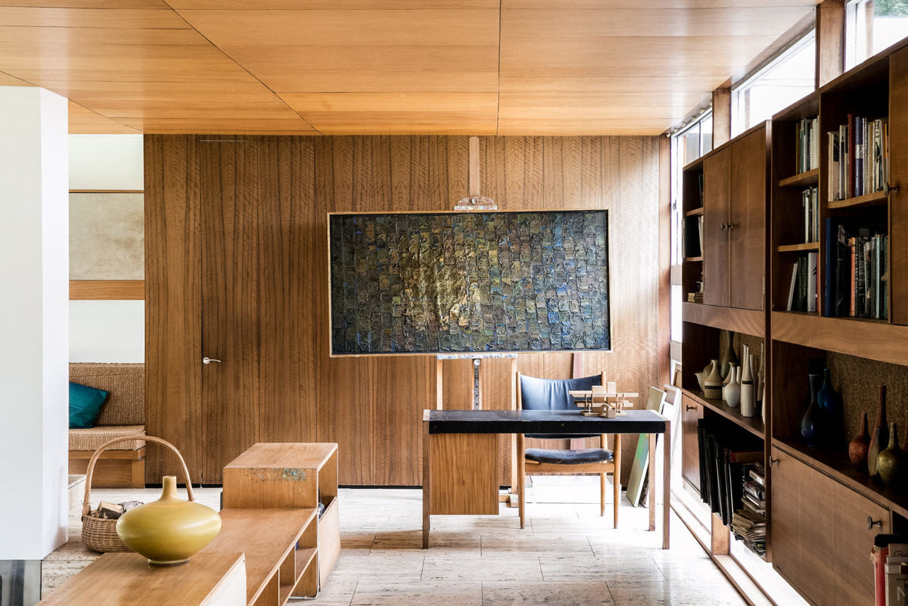 The stylish and elegant interior of Bernat Klein's house, showing his desk and a painting behind.