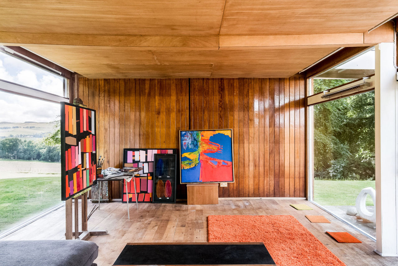 The stylish and elegant interior of Bernat Klein's house, showing his paintings, in reds and yellows, decorating the space.