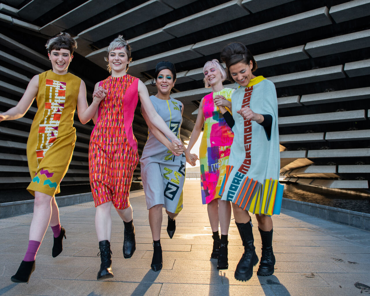 Five models wearing a range of Quant-inspired garments in bright colours. They are photographed running together and smiling in front of the museum.