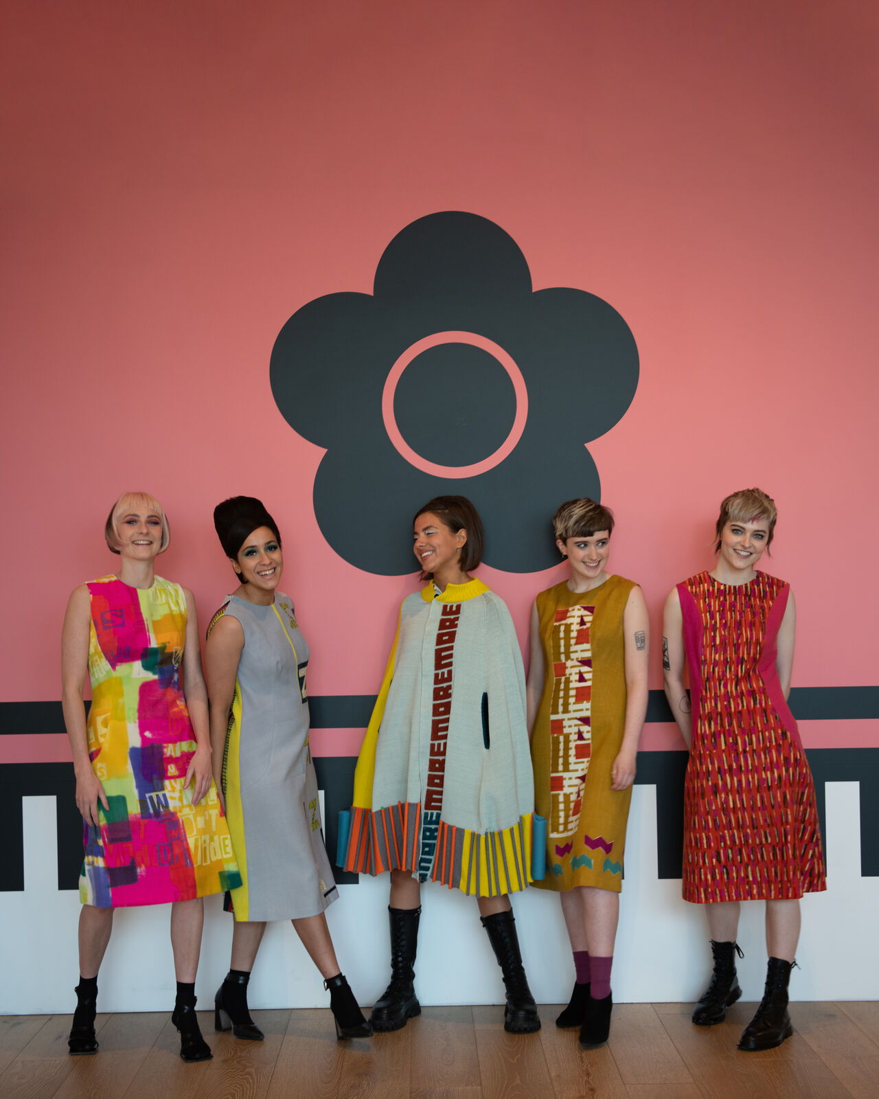 Five models wearing a range of Quant-inspired garments in bright colours. They are photographed in front of the Quant Daisy logo.