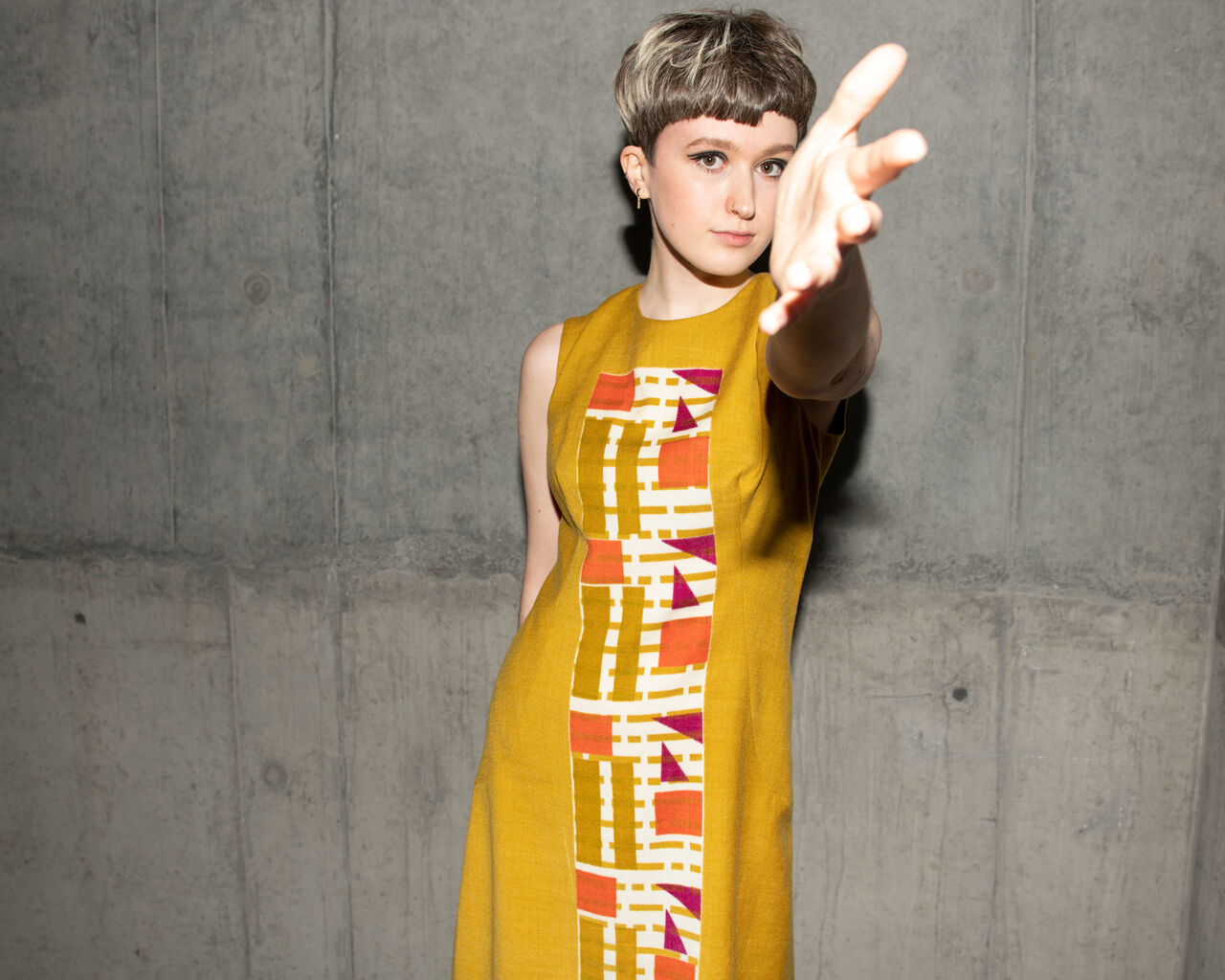 A model wearing a bright colourful, Mary Quant-inspired garment.