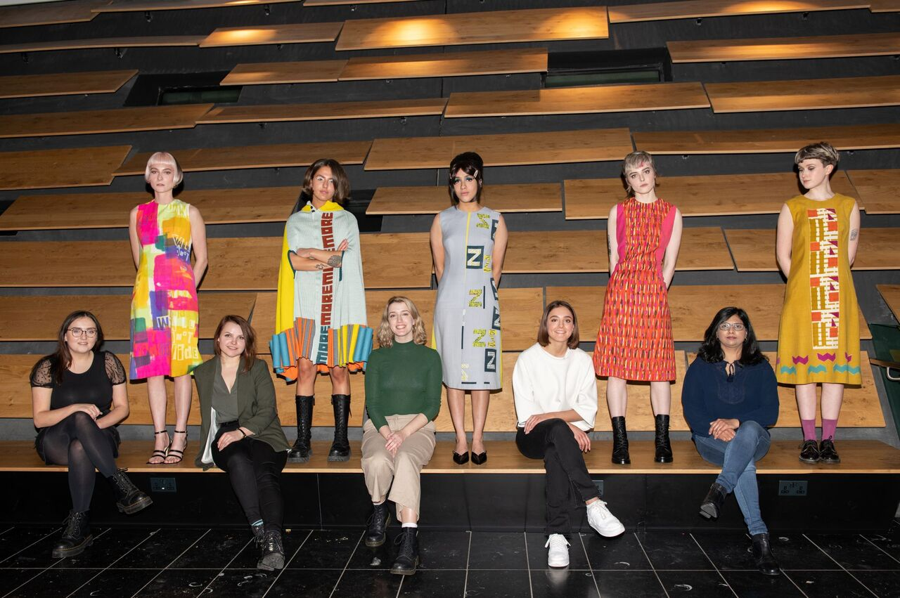 Five models wearing a range of Quant-inspired garments in bright colours. They are photographed on a long bench against oak panelling in the museum.