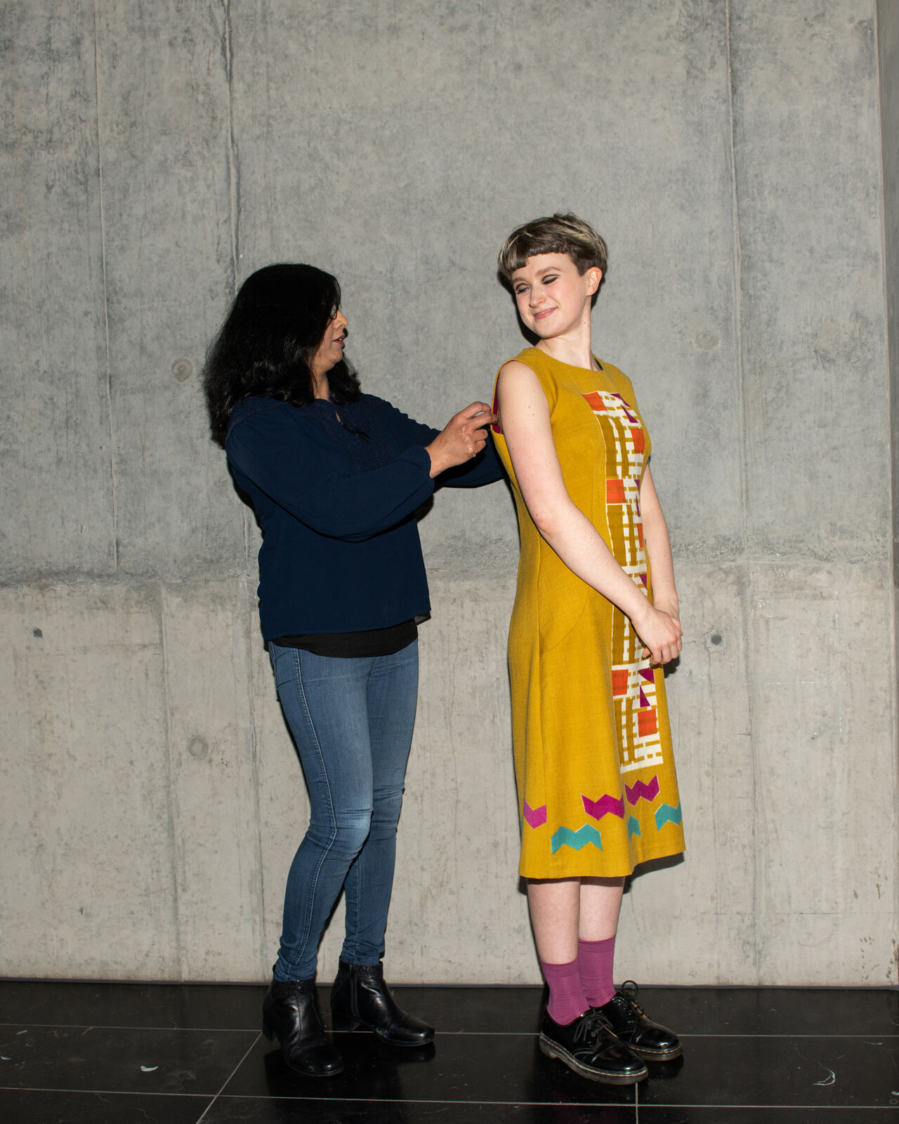 A model wearing a bright colourful, Mary Quant-inspired garment and having it adjusted by the designer.