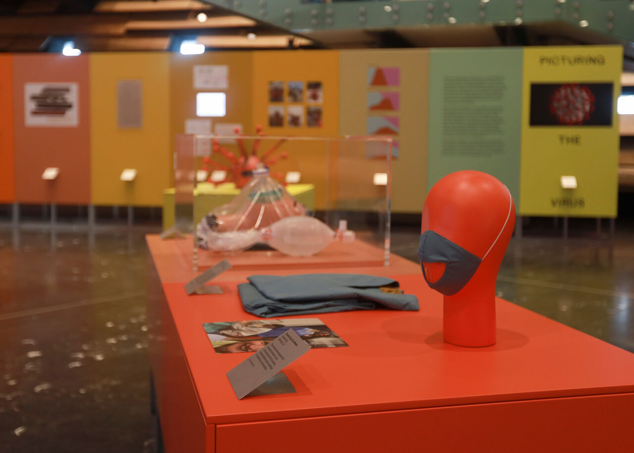 Now Accepting Contactless exhibition in V&A Dundee. Close-up of red plinths with a range of objects on them.