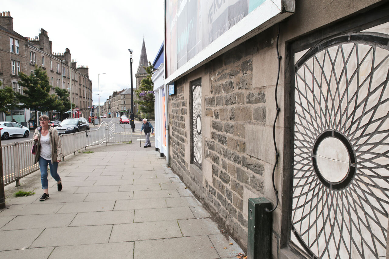 Photo of a street in Dundee with small blocked up windows that have been filled with a geometric pattern of ceramic tiles.